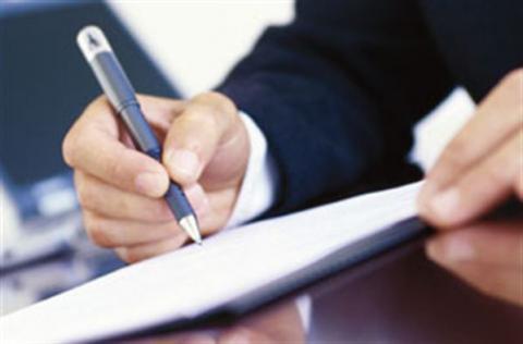 Gros plan sur les mains d'un homme qui écrit sur un papier.