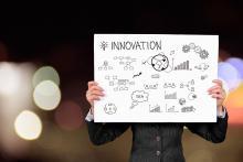 Un homme tenant une pancarte avec des rouages et des visuels relatif à l'innovation.