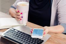 Une femme travaille devant son ordinateur, téléphone et café en main.