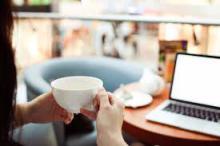 Une personne travaillant depuis chez elle avec un café à la main.